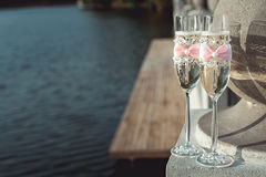 Two wedding champagne glasses with a bow on a stone railing. Lake promenade at sunset Stock Photos