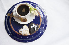 Two wedding cookies with a cup of coffee on the plate Stock Images