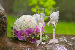 Two wedding glasses and bridal bouquet in summer garden Royalty Free Stock Images