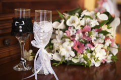 Two wedding glasses and bridal bouquet on table Royalty Free Stock Images