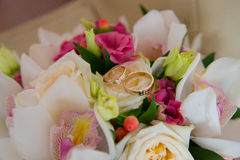 Two wedding gold rings with a diamond lying on the bride's bouquet of white orchids and pink flowers. Stock Images
