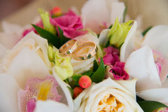 Two wedding gold rings with a diamond lying on the bride's bouquet of white orchids and pink flowers. Stock Photo