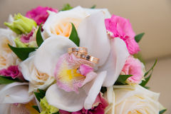 Two wedding gold rings with a diamond lying on the bride's bouquet of white orchids and pink flowers. Royalty Free Stock Photo