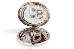 Two wedding gold rings in a small round glass mirror. Two wedding rings made of white gold in a small round glass mirror on a white background isolated Stock Photo
