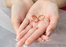 Two wedding rings. On the palms of the bride Stock Photo
