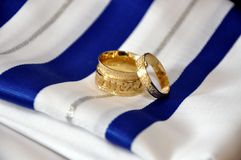 Two wedding gold rings. On white-blue cotton tradition tissue Royalty Free Stock Photo
