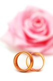 Two wedding rings. And pink rose at the background Royalty Free Stock Photos