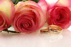 Two wedding rings. With tree roses as a background Stock Images