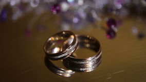 Two wedding rings. Two beautiful wedding rings on glass, mirror table.Wedding concept stock video
