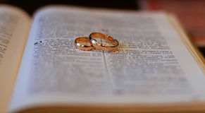 Two wedding rings on a bible Stock Images