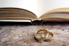 Two wedding rings with a bible. On wooden table Stock Photography
