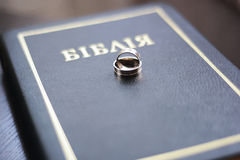 Two wedding rings with a bible on wooden table. Two wedding rings with a bible on table Royalty Free Stock Images