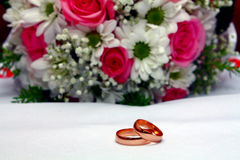 Two wedding rings and bouquet Royalty Free Stock Images
