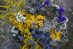 Two wedding rings on a bouquet of bright blue and yellow flowers, wedding, proposal, lifestyle-concept Stock Images