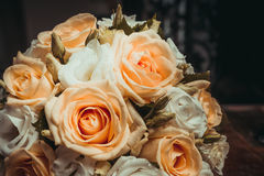 Two wedding rings and a bouquet of orange and white roses. Stock Photos