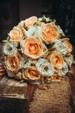 Two wedding rings and a bouquet of orange and white roses. Royalty Free Stock Photo