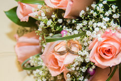 Two  wedding rings on a bouquet of pink roses. Two beautiful wedding rings on a bouquet of pink roses Royalty Free Stock Image