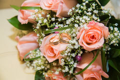 Two  wedding rings on a bouquet of pink roses. Two beautiful wedding rings on a bouquet of pink roses Stock Images