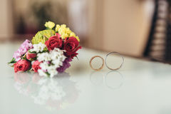 Two wedding rings and a boutonniere groom. Two wedding rings are reflected in the table and next to the boutonniere of the groom Royalty Free Stock Photos