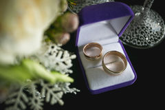 Two wedding rings in box lying next to white roses stock photos