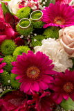 Two wedding rings on a bridal colorful bouquet Stock Images