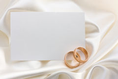 Two wedding rings and card. Two gold wedding rings with card over white satin Royalty Free Stock Photography