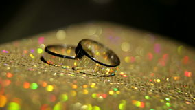 Two wedding rings on a colorful shining background. Jewelry stock video