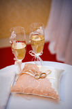 Two wedding rings on a cushion on the background glasses of cham Stock Photos