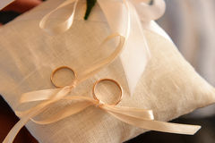 Two wedding rings on a cushion tied with ribbon Stock Photos