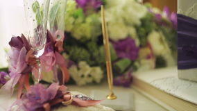 Two wedding rings on a cushion tied with ribbon and other attributes stock footage
