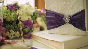 Two wedding rings on a cushion tied with ribbon and other attributes.  stock video