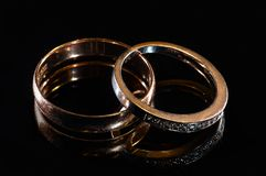 Two wedding rings of different sizes made in gold on the black mirror surface royalty free stock image