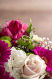 Two wedding rings on flowers of a bridal colorful bouquet. With purple daisies, white carnations and pale pink roses Royalty Free Stock Photo