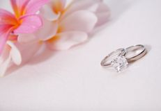 Two wedding rings in front of tropical flowers Stock Photo