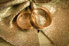 Two wedding rings on glittery surface. Two gold wedding rings on glittery yellow surface Royalty Free Stock Photo