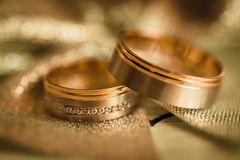 Two wedding rings on glittery surface. Two gold wedding rings on glittery surface with blurred background Stock Photo