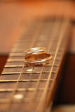Two wedding rings are on guitar stripes Royalty Free Stock Image
