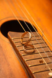 Two wedding rings are on guitar stripes Royalty Free Stock Images