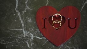 Two wedding rings and i love you sign. On green marble background stock video