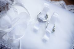 Two Wedding Rings In Ribbon On Pillow Stock Photos