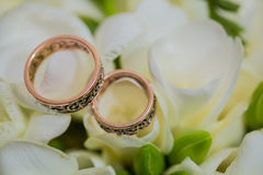Two wedding rings in infinity sign. Love concept. Two wedding rings in infinity sign with bouquet on black background. Love concept stock photography