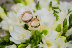 Two wedding rings in infinity sign. Love concept. Two wedding rings in infinity sign with bouquet on black background. Love concept royalty free stock photography
