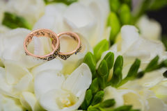 Two wedding rings in infinity sign. Love concept. Two wedding rings in infinity sign with bouquet on black background. Love concept royalty free stock photo