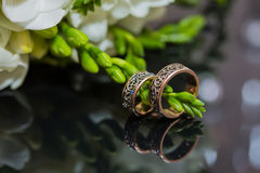 Two wedding rings in infinity sign. Love concept. Two wedding rings in infinity sign with bouquet on black background. Love concept royalty free stock image