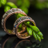 Two wedding rings in infinity sign. Love concept. Two wedding rings in infinity sign with bouquet on black background. Love concept royalty free stock photos