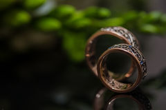 Two wedding rings in infinity sign. Love concept. Two wedding rings in infinity sign with bouquet on black background. Love concept stock image