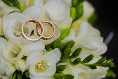 Two wedding rings in infinity sign. Love concept. Two wedding rings in infinity sign with bouquet on black background. Love concept royalty free stock images