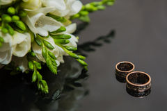 Two wedding rings in infinity sign. Love concept. Two wedding rings in infinity sign with bouquet on black background. Love concept stock images