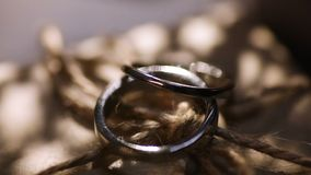 Two wedding rings on a kraft box. Dark scene.  stock video