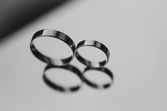 Two wedding rings laying on a mirror. black and Stock Photography